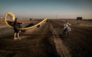 Mann mit aufgepumpten Kite steht am Straßenrand und zeigt mit dem Daumen nach oben, Motorrad fährt vorbei