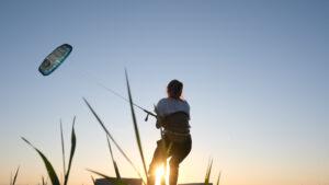 Mädchen beim Landkiten im Sonnenuntergang