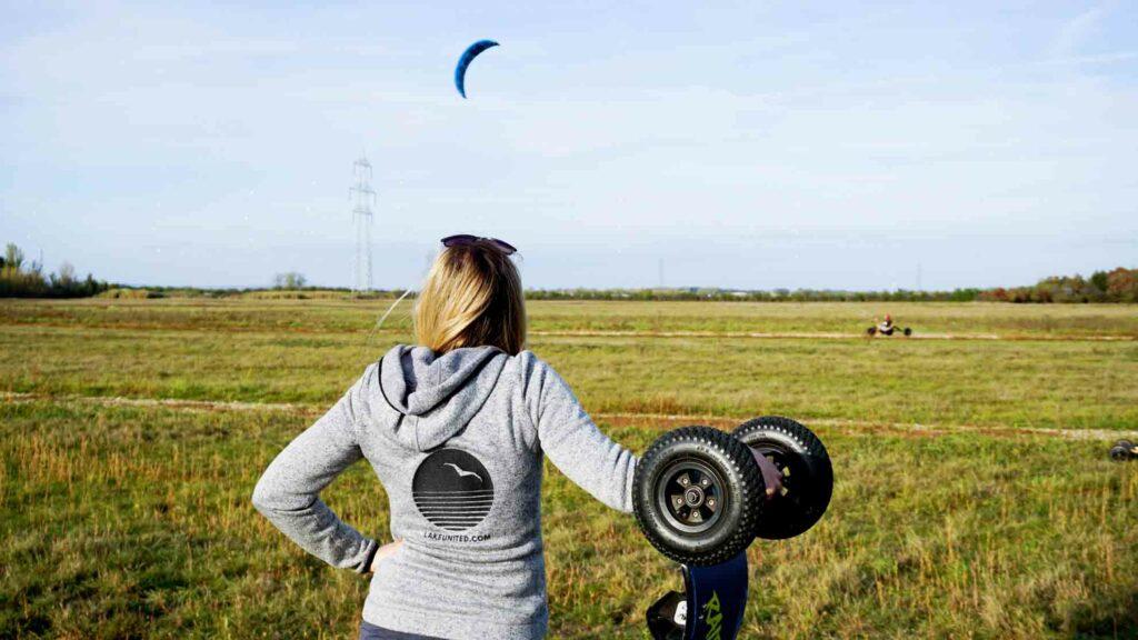 Mädchen steht mit Mountainboard und beobachtet einen Buggy-Kiter