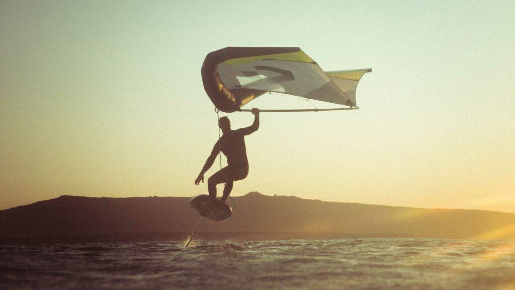 Surfer mit Wing und Hydrofoilboard im Wasser
