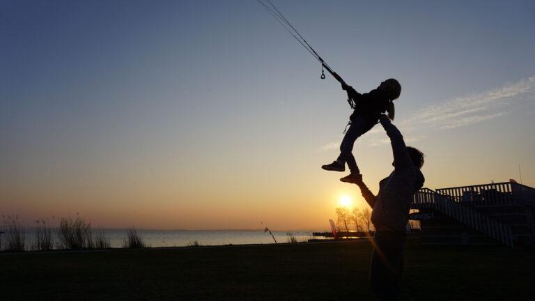 Kind beim Landkiten zu Sonnenuntergang