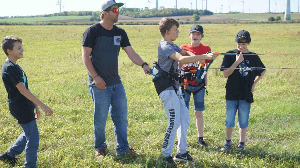 Kitelehrer hält Schüler am Trapez fest