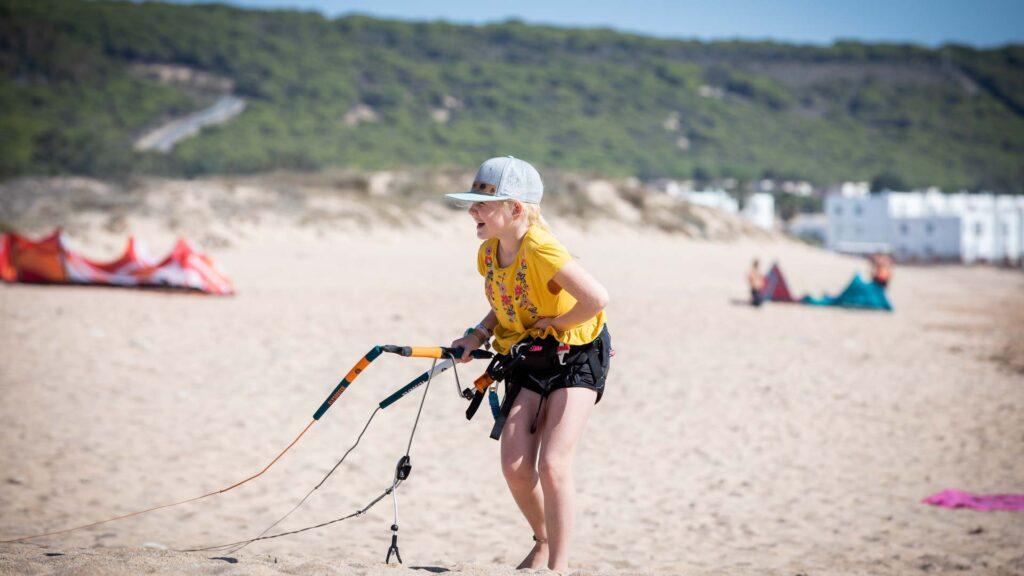 Kind steht am Strand und hat Spaß beim Landkiten