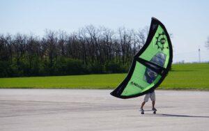 Wingfoiler mit Skateboard am Asphalt