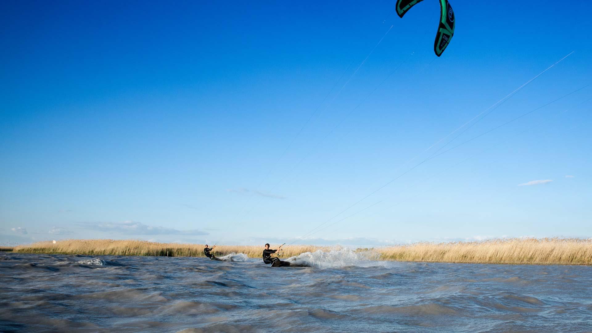 Olsen und Patrick kiten am Neusiedlersee mit Schilf im Hintergrund