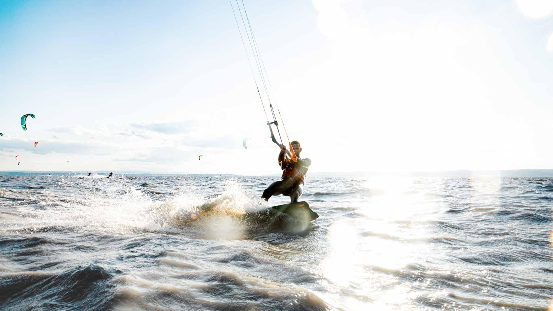Kitesurfer kitet mit Sonnenschein im Hintergrund über den Neusiedlersee