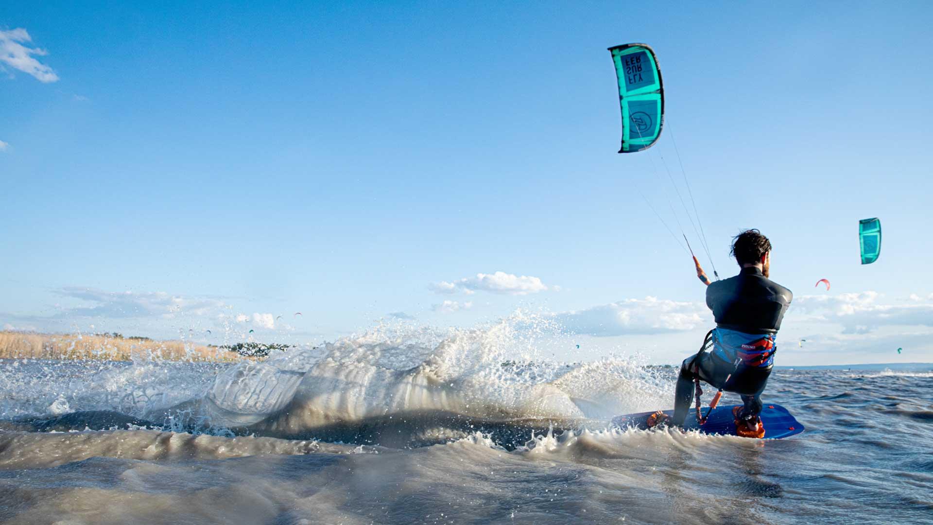 Kitesurfer surft nach rechts und erzeugt viel Spray