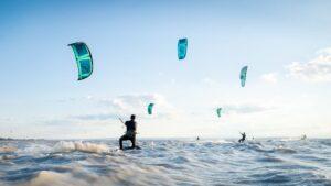 Fünf Kitesurfer surfen gemeinsam in der Gruppe über den Neusiedlersee