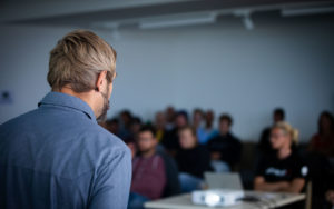 Mann hält einen Vortrag vor vielen Zuhörern