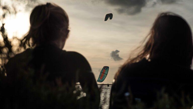 2 Personen schauen Kiter im Wasser zu