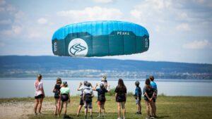 Landkiten mit dem Flysurfer Peak. Viele Kinder stehen im Kreis und schauen zu