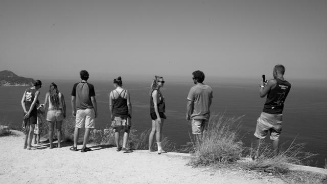 Gruppe Menschen steht auf einem Berg und blickt ins Meer