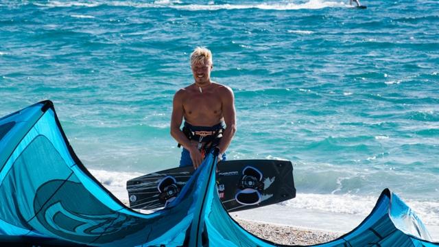 Mann steht mit Board am Ufer und lächelt