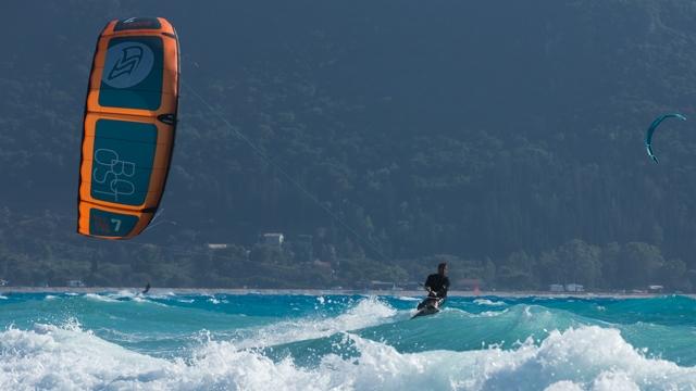 Kitesurfer mit orangem Flysurfer Kite im Meer