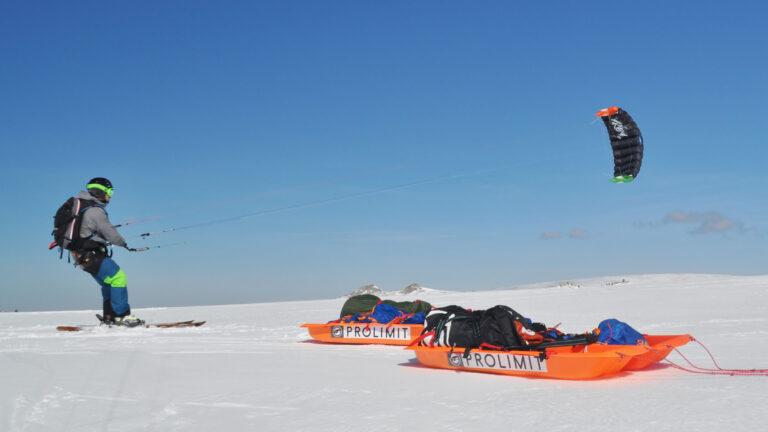 Snowkiter im Schnee mit 2 Schlitten