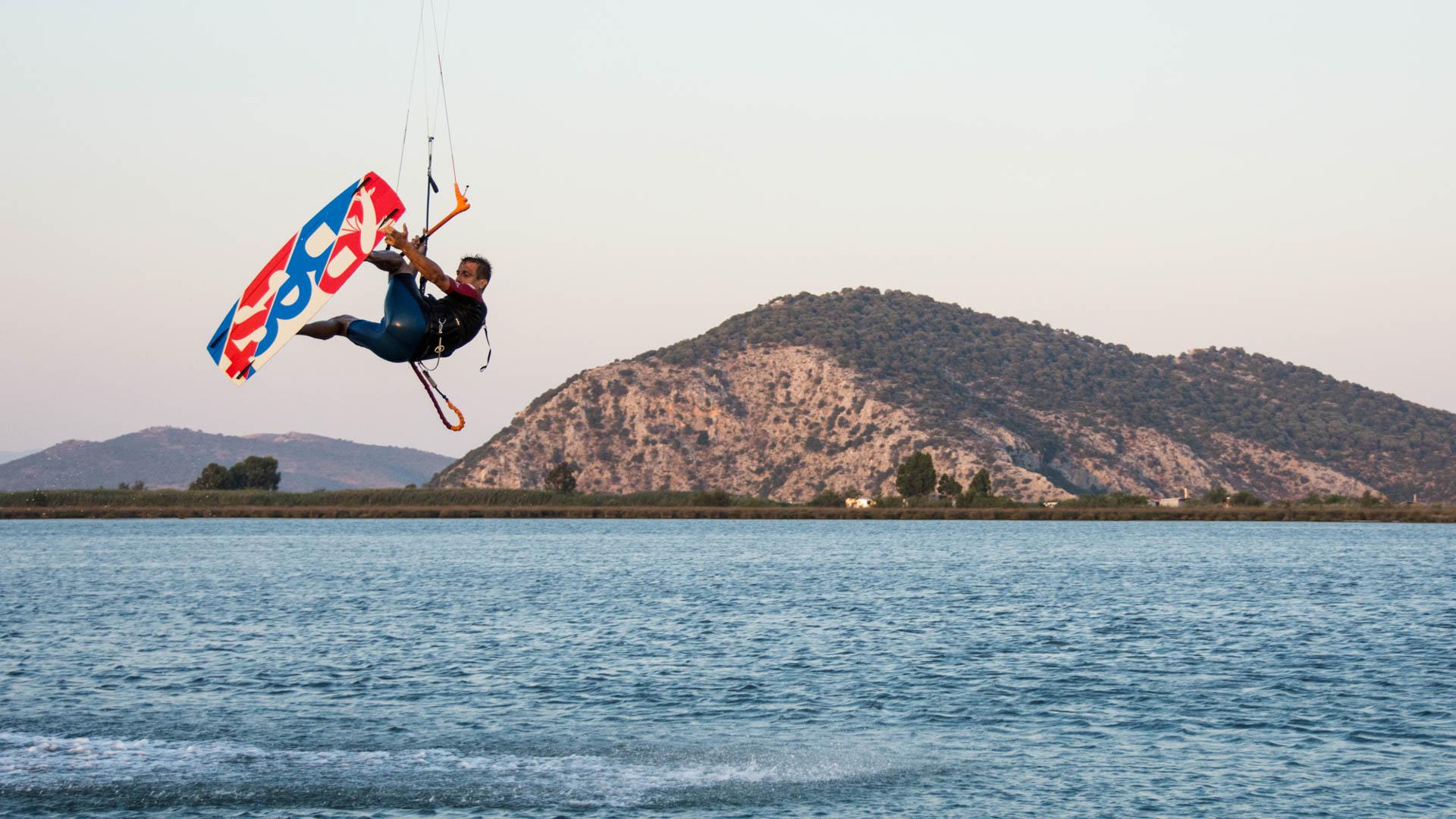 Kiter springt und greift aufs Board