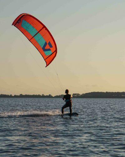 Dame kitet mit rotem Duotone Kite in der Lagune