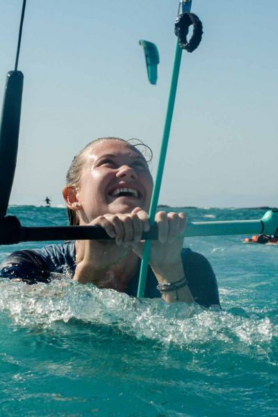 Lachende Person hält die Bar im Meer