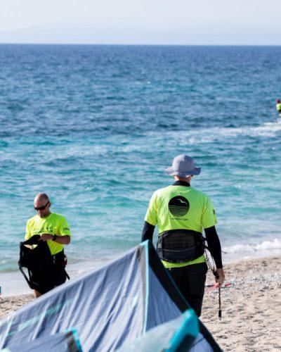 Kitesurfer in LakeUnited Shirts machen sich am Strand zwischen ihren aufgebauten Kites für die nächste Session fertig.