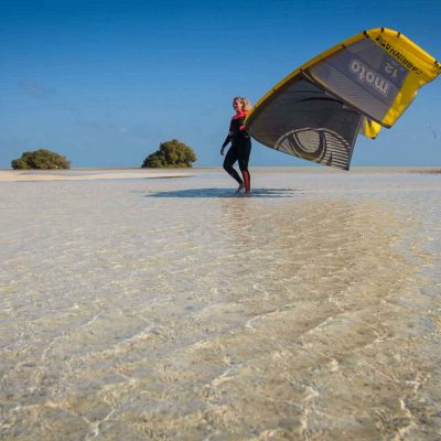 Mädchen spaziert mit Kite am Arm durch seichtes klares Wasser