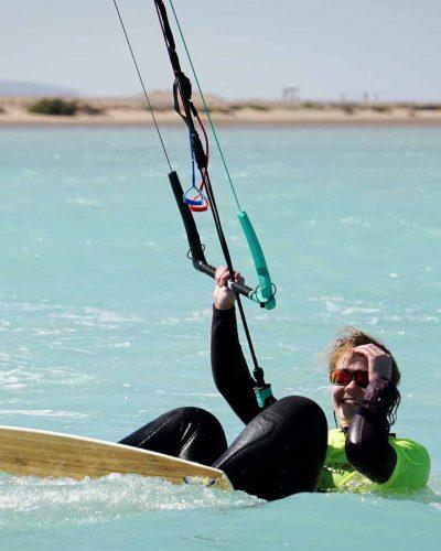 lachende Frau mit Kite und Board liegt im Wasser und macht Pause