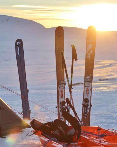Skiequipment steckt neben Zelt im Schnee