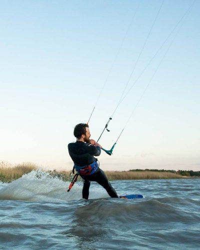 Kitesurfer vor Schilf im Wasser