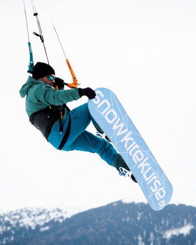 Olsen springt mit Snowboard und macht einen Grab