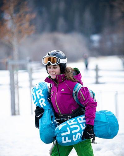 Dame trägt 2 Snowkites und lächelt
