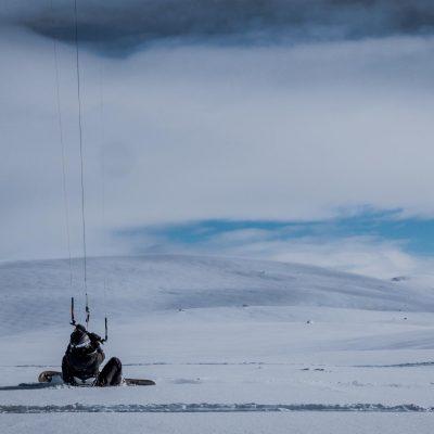 Person sitzt mit Snowboard und Kite im Pulverschnee