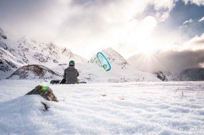 Snowboarder sitzt mit Kite am Berg und blickt richtung Sonne