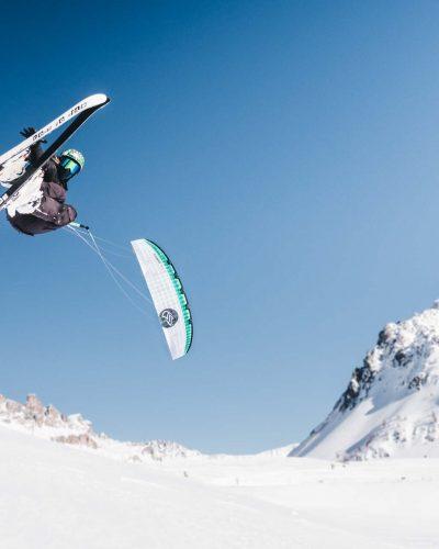 Schifahrer springt mit Kite im Schnee