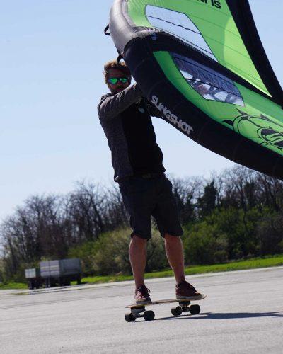 Mann mit Wing und Skateboard über den Asphalt